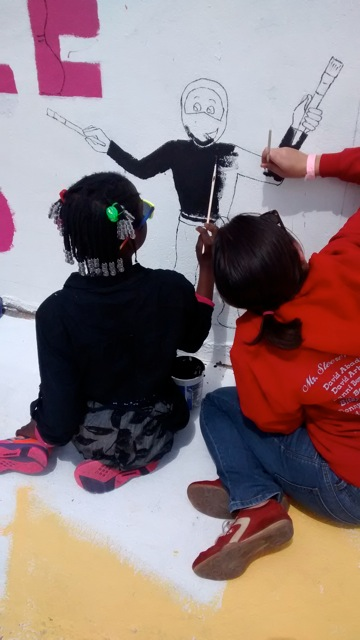 Youth painting the mural